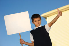 The schoolboy with the white blank. Board against the house Royalty Free Stock Images