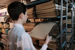A schoolboy in a white shirt pulls out an old book from a bookshelf. A student in the library or in the archive room is looking stock photos