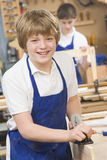Schoolboy in woodwork class. Smiling royalty free stock photo