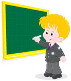 Schoolboy writes on the blackboard. Elementary school student writing with chalk on the school blackboard Stock Photography