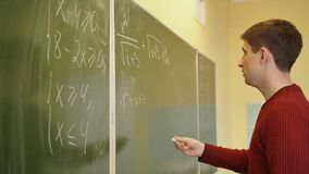 A schoolboy writes on the blackboard during a math lesson. A schoolboy writes on the blackboard during a math lesson stock video