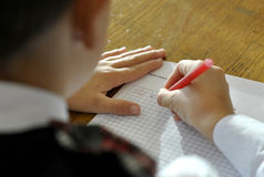Schoolboy writes in a notebook Royalty Free Stock Photo