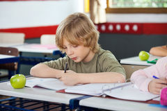 Schoolboy Writing On Book In Classroom Stock Photo