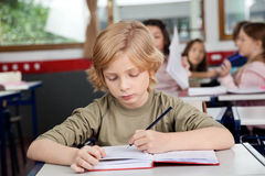 Schoolboy Writing In Book At Desk. Cute schoolboy writing in book at desk with classmates in background Royalty Free Stock Photo