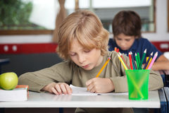 Schoolboy Writing In Book At Desk Stock Images
