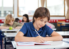Schoolboy Writing In Book At Desk Stock Photo