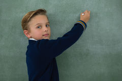Schoolboy writing with chalk on chalkboard. Portrait of schoolboy writing with chalk on chalkboard Stock Photography