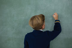 Schoolboy writing with chalk on chalkboard. Portrait of schoolboy writing with chalk on chalkboard Stock Images