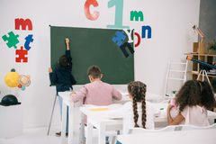 Schoolboy writing on chalkboard while classmates studying at desks Royalty Free Stock Image