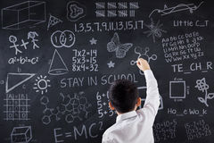 Schoolboy writing doodles on chalkboard. Back view of a little schoolboy writing doodles on the blackboard, shot in the classroom Stock Photography