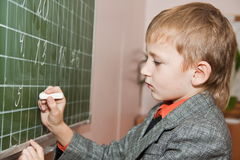 Schoolboy writing jn the board Royalty Free Stock Photo