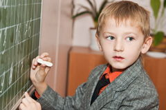 Schoolboy writing jn the board Stock Photography