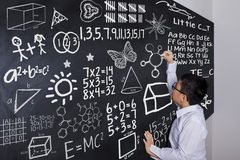 Schoolboy writing mathematics formula. Male elementary school student writing mathematics formula on the blackboard, shot in the class Stock Image