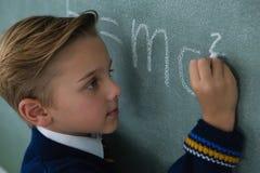 Schoolboy writing maths formula on chalkboard. Adorable schoolboy writing maths formula on chalkboard Royalty Free Stock Image