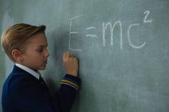 Schoolboy writing maths formula on chalkboard Stock Image