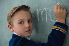 Schoolboy writing maths formula on chalkboard. Portrait of schoolboy writing maths formula on chalkboard Stock Photo