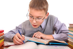 Schoolboy writing. At the School Desk on the white background Royalty Free Stock Photos