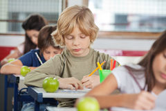 Schoolboy Writing While Sitting At Desk Royalty Free Stock Image
