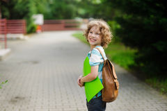 Schoolboy of 8-9 years stand in a half-turn to the camera and joyfully smiles. The boy has a nice face, a fair hair, an open look. It has behind shoulders a Royalty Free Stock Images