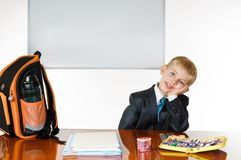 Schoolboy. Young schoolboy with desk satchel and blackboard on white background. thinking Royalty Free Stock Photo