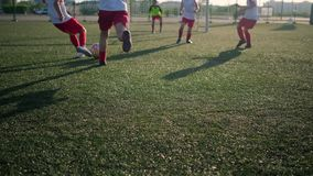 Schoolboys in football uniform score goal low angle shot. Young guys schoolboys in football uniform score goal playing soccer on pitch low angle shot stock video footage