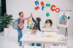 Schoolboys giving high five while schoolgirls studying in classroom Stock Photos