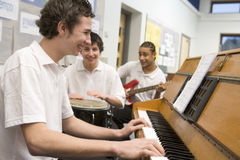 Schoolboys playing musical instruments Royalty Free Stock Photos