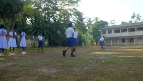 Schoolboys prepare to game on playground against school. Colombo/Sri Lanka - April 05 2019: Schoolboys prepare to game on playground against school building and stock footage