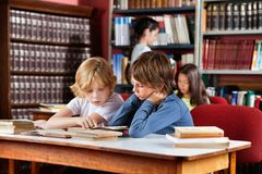Schoolboys Reading Book Together In Library. Little schoolboys reading book together while sitting at table in library with classmates in background Royalty Free Stock Image