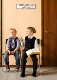 Schoolboys are sitting beside the principal's office Royalty Free Stock Photos