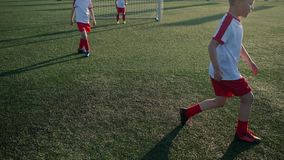 Schoolboys in uniform dribble ball and score goal. During intensive training on sunny day stock video