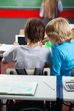 Schoolboys Using Digital Tablet At Desk Royalty Free Stock Photos