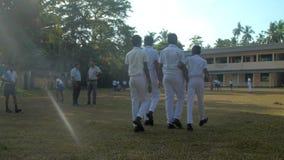 Schoolboys walk along green playground to school building. Colombo/Sri Lanka - April 05 2019: Schoolboys in white uniforms walk along green playground to school stock footage