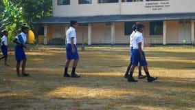 Schoolboys walk along playground against school building. Colombo/Sri Lanka - April 05 2019: Schoolboys walk along playground against school building on last day stock video
