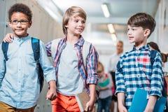 three adorable schoolboys walking stock photography