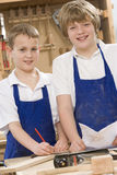 Schoolboys in woodwork class. Smiling royalty free stock images