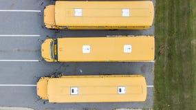 Schoolbussen op School worden geparkeerd die Stock Foto