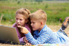 Schoolchild. Boy and girl lying on the lawn and do on your laptop royalty free stock image