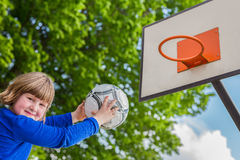 Schoolchild aiming ball at board with basket Royalty Free Stock Image