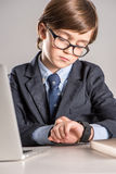 Schoolchild in business suit looking at smartwatch Royalty Free Stock Images
