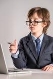 Schoolchild in business suit with pen in hands Stock Photo