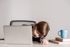 Schoolchild in business suit sleeping on desk Stock Photography