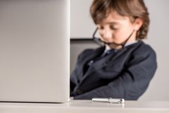 schoolchild in business suit sleeping near laptop Royalty Free Stock Images