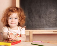 Schoolchild in a class. Funny smiling schoolchild in a class against blackboard royalty free stock images