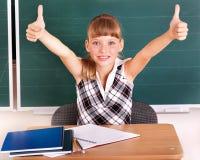 Schoolchild in classroom near blackboard. Stock Photo