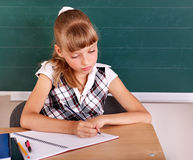Schoolchild in classroom near blackboard. Royalty Free Stock Photo