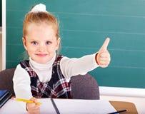 Schoolchild in classroom near blackboard. Stock Image