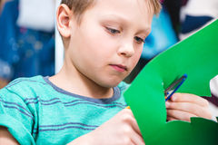 Schoolchild cutting green paper. Close-up portrait of schoolchild cutting green paper with scissors Royalty Free Stock Images