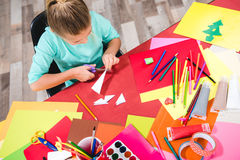 Schoolchild cutting paper. Schoolchild sitting at table with school supplies and cutting white paper Royalty Free Stock Image
