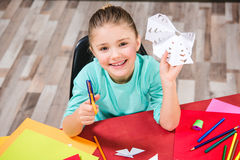 Schoolchild cutting paper. Schoolchild cutting white paper and smiling at camera Stock Photos
